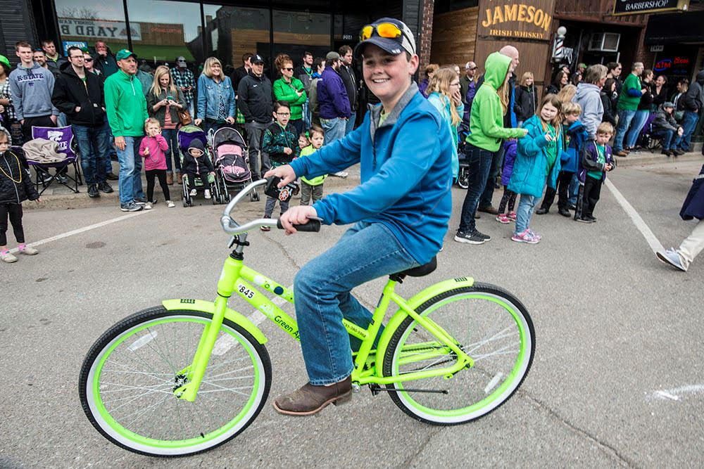 Boy riding Green Apple Bike in 2018 St. Patty's Day Parade